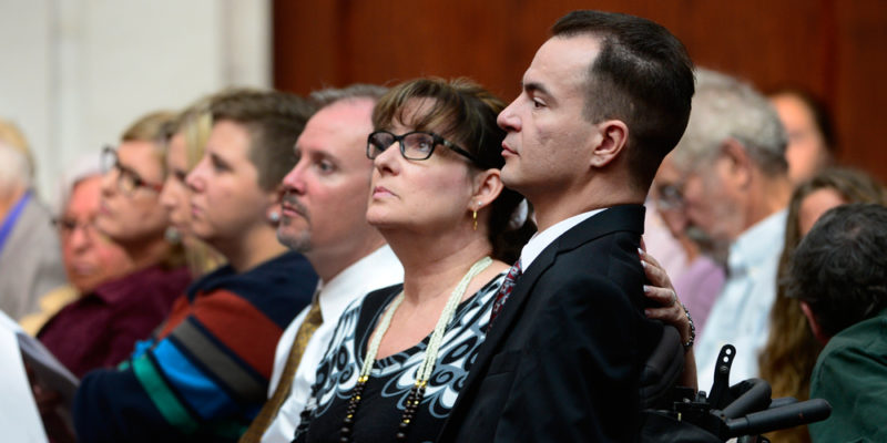 Brandon Coats, right, waits for the proceedings to begin with his mother Donna Scharfenberg sitting by his side.